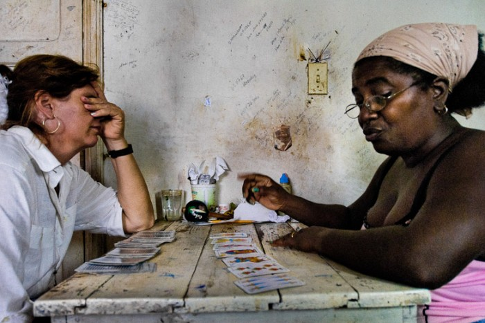 A Cuban woman consults her health problem with a fortune teller, practitioner of a Afro-Cuban religion, in Santiago de Cuba, Cuba, August 4, 2008. The Palo religion (Las Reglas de Congo) belongs to the group of syncretic religions which developed in Cuba amongst the black slaves, originally brought from Congo during the colonial period. Palo, having its roots in spiritual concepts of the indigenous people in Africa, worships the spirits and natural powers but can often give them faces and names known from the Christian dogma. Although there have been strong religious restrictions during the decades of the Cuban Revolution, the majority of Cubans still consult their problems with practitioners of some Afro Cuban religion.